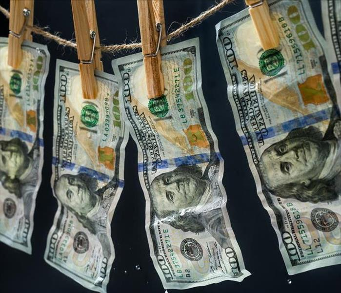 Hundred dollar bills hanging on a clothes dryer line.