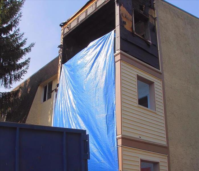 Apartment building, the top floor burned. Bottom two floors tarped off, with a dumpster outside the building.